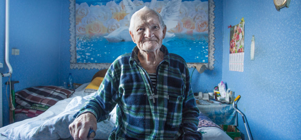 Elderly man wearing a blue and green checkered fleece, sitting at the end of a bed in an entirely blue room. He is resting on a brown walking stick and on the wall behind his head is a very large painting of two swans.