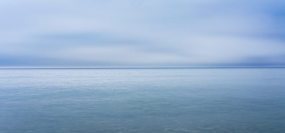 A photo looking out to sea at the horizon. The sky and sea are similar shades of cool blue.